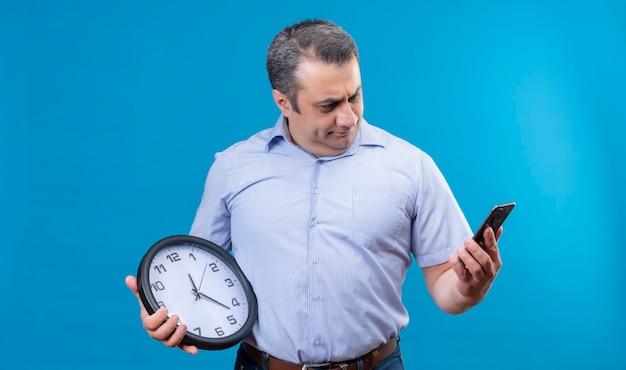 Denkender mann mittleren alters, der handy betrachtet, während wanduhr auf einem blauen hintergrund hält