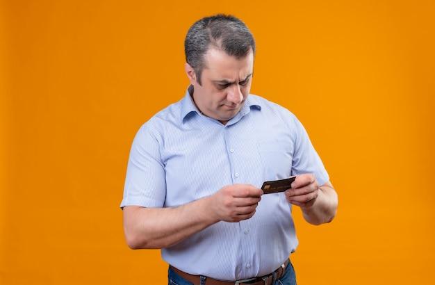 Denkender mann mittleren alters in blau gestreiftem betrachten der kreditkarte auf einem orangefarbenen hintergrund