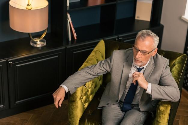 Denkender mann. seitenansicht eines älteren mannes, der in einem mit samt gepolsterten sessel sitzt, während er sich auf seine arme stützt und wegschaut