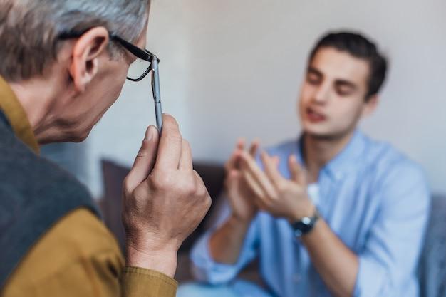 Denkender psychologe mit bleistift hörender junger mann