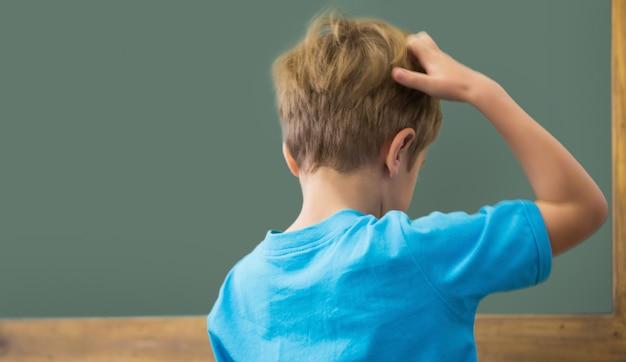 Denkender schüler, der seinen kopf im klassenzimmer verkratzt