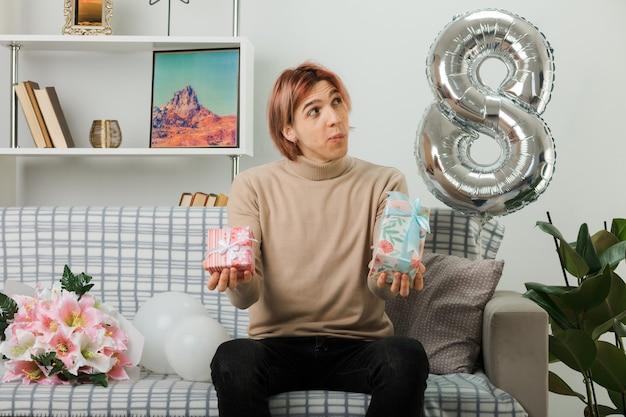 Denkender seitlich gutaussehender kerl am glücklichen frauentag, der geschenk hält. auf dem sofa im wohnzimmer sitzen