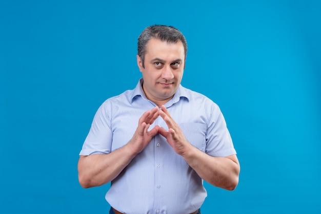Denkender und verwirrter mann mittleren alters im blauen gestreiften hemd, das hände zusammen auf einem blauen hintergrund hält