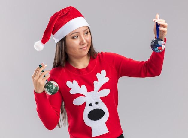 Denkendes junges asiatisches mädchen mit weihnachtsmütze mit pullover, das weihnachtsbaumkugeln auf weißem hintergrund hält und betrachtet