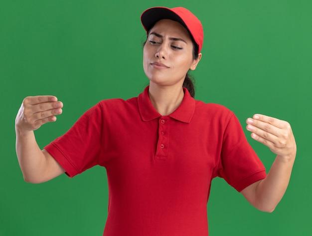 Denkendes junges liefermädchen in uniform und mütze, das vorgibt, etwas isoliert auf grüner wand zu halten