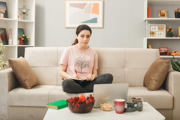 Denkendes junges mädchen, das ein notebook auf dem sofa hinter dem couchtisch hält und einen laptop im wohnzimmer betrachtet
