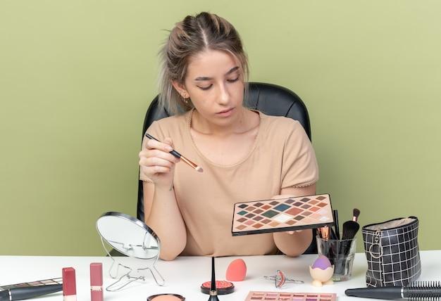 Denkendes junges schönes mädchen, das am tisch mit make-up-tools sitzt und pinsel mit lidschatten-palette einzeln auf olivgrünem hintergrund hält und betrachtet