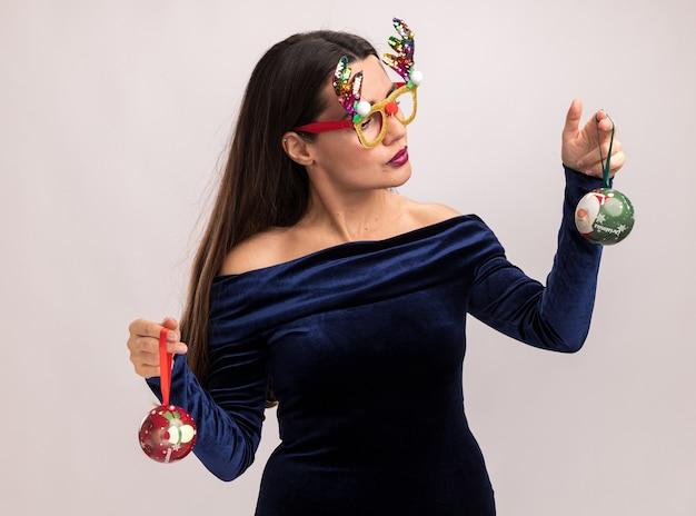 Denkendes junges schönes mädchen, das blaues kleid und weihnachtsbrille hält und weihnachtskugeln lokalisiert auf weißem hintergrund trägt