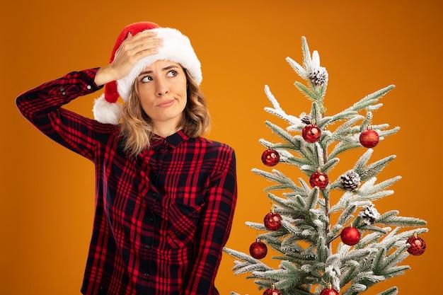 Denkendes junges schönes mädchen, das in der nähe des weihnachtsbaums mit weihnachtsmütze steht und die hand auf den kopf legt, isoliert auf orangefarbenem hintergrund
