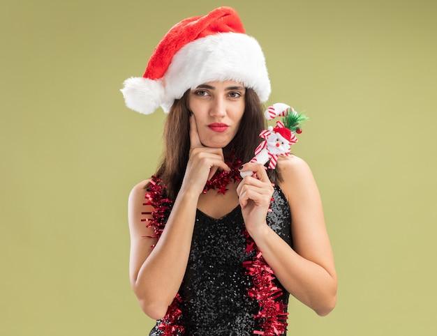 Denkendes junges schönes mädchen, das weihnachtsmütze mit girlande am hals trägt und weihnachtsspielzeug hält, das finger auf die wange legt, isoliert auf olivgrünem hintergrund