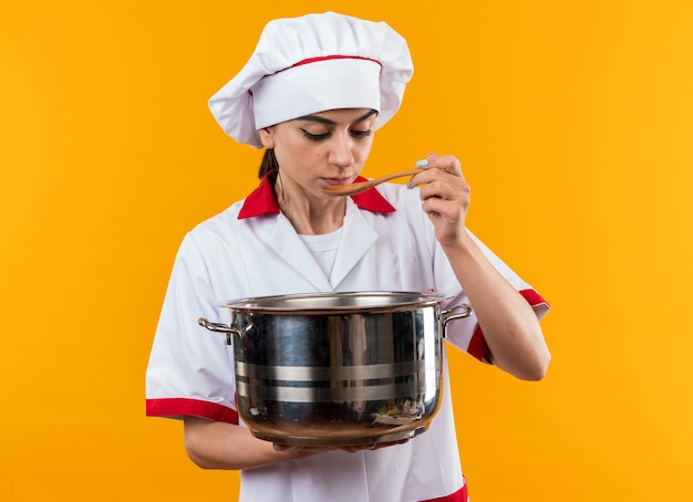 Denkendes junges schönes mädchen in kochuniform, das kochtopf hält und suppe versucht