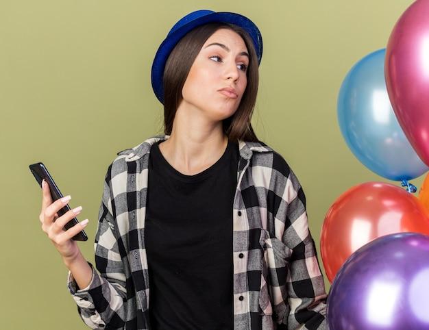 Denkendes junges schönes mädchen mit blauem hut, das in der nähe von ballons steht und das telefon isoliert auf olivgrüner wand hält?