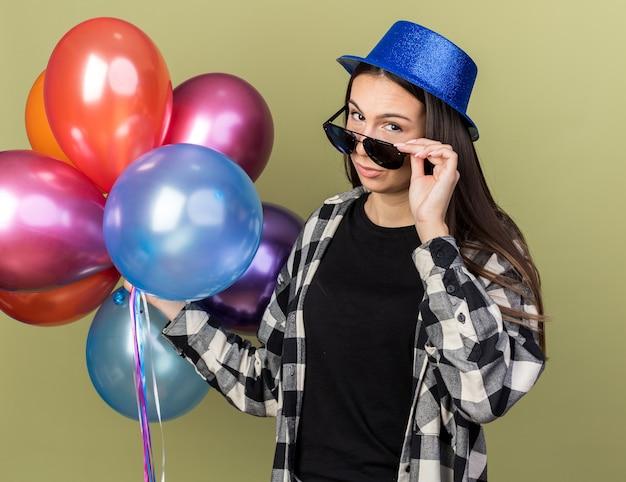 Denkendes junges schönes mädchen mit blauem hut mit brille mit ballons
