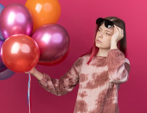 Denkendes junges schönes mädchen mit brille, das ballons hält und betrachtet