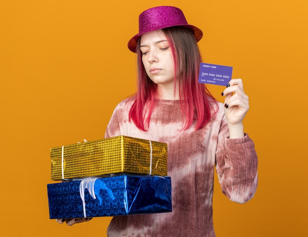 Denkendes junges schönes mädchen mit partyhut, das geschenkboxen mit kreditkarte hält