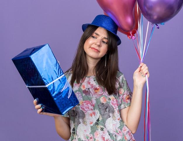 Denkendes junges schönes mädchen mit partyhut, das luftballons hält und die geschenkbox in der hand betrachtet