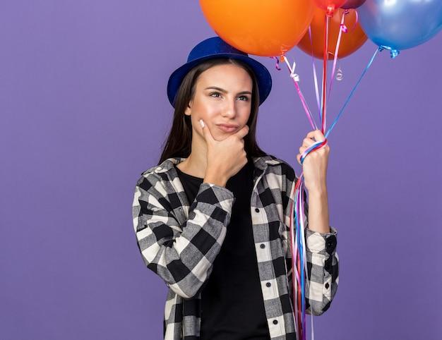 Denkendes junges schönes mädchen mit partyhut mit luftballons packte das kinn isoliert auf blauer wand