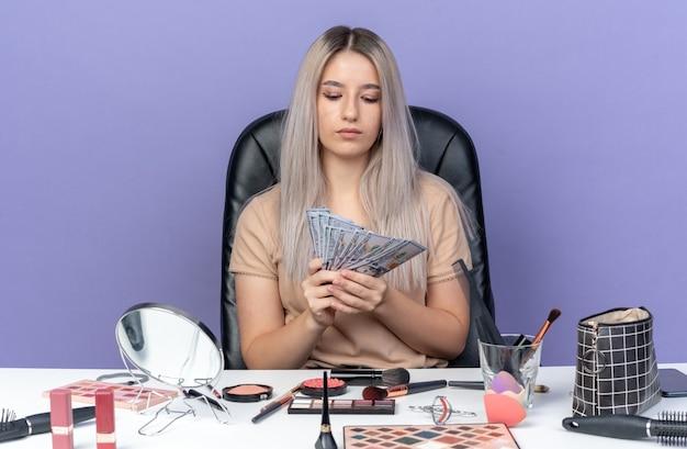 Denkendes junges schönes mädchen sitzt am tisch mit make-up-tools, die bargeld auf blauem hintergrund halten und betrachten