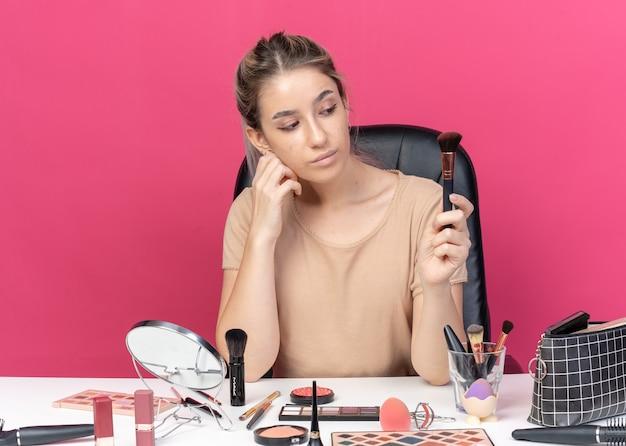 Denkendes junges schönes mädchen sitzt am tisch mit make-up-tools, die den pulverpinsel auf rosafarbenem hintergrund halten und betrachten