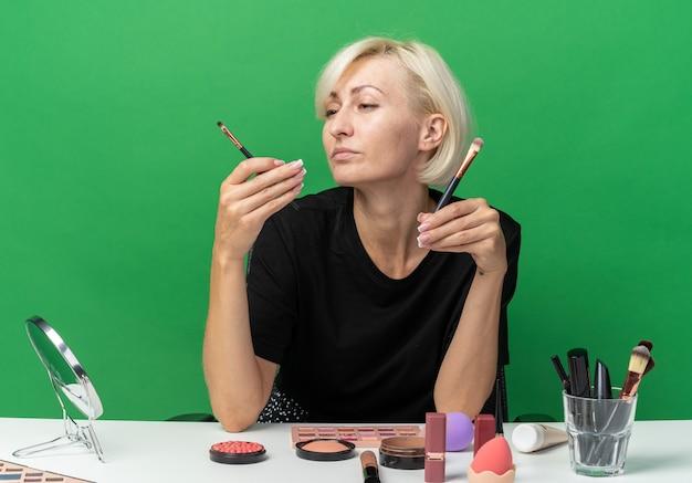 Denkendes junges schönes mädchen sitzt am tisch mit make-up-tools, die make-up-pinsel auf grünem hintergrund halten und betrachten