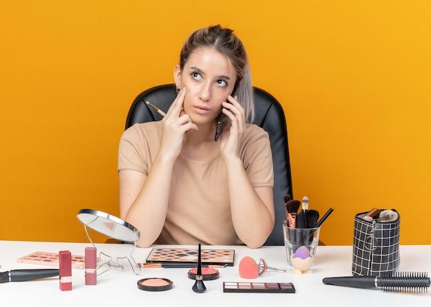 Denkendes junges schönes mädchen sitzt am tisch mit make-up-tools, die make-up-pinsel halten, spricht am telefon einzeln auf orangefarbenem hintergrund