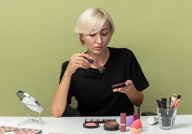 Denkendes junges schönes mädchen sitzt am tisch mit make-up-tools, die puderröte einzeln auf olivgrünem hintergrund halten und betrachten