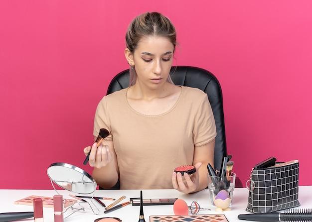 Denkendes junges schönes mädchen sitzt am tisch mit make-up-tools, die puderröte einzeln auf rosafarbenem hintergrund halten und betrachten