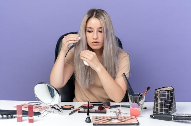 Denkendes junges schönes mädchen sitzt am tisch mit make-up-tools und hält haarcreme isoliert auf blauem hintergrund