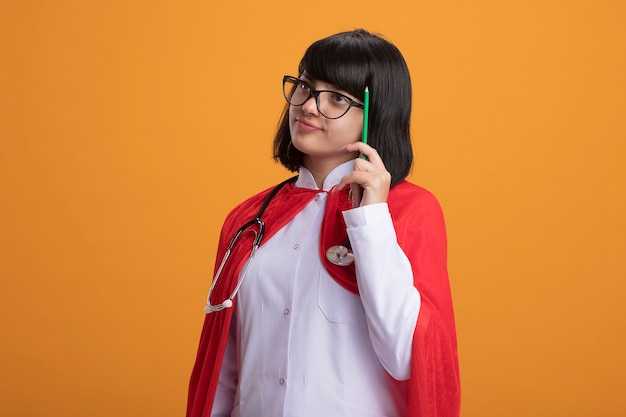Denkendes junges superheldenmädchen, das stethoskop mit medizinischem gewand und umhang mit brille trägt, die kopf mit bleistift kratzt