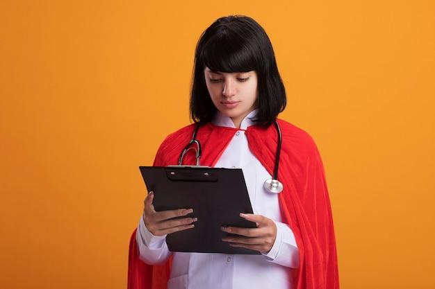 Denkendes junges superheldenmädchen, das stethoskop mit medizinischer robe und umhang trägt, die zwischenablage halten und betrachten