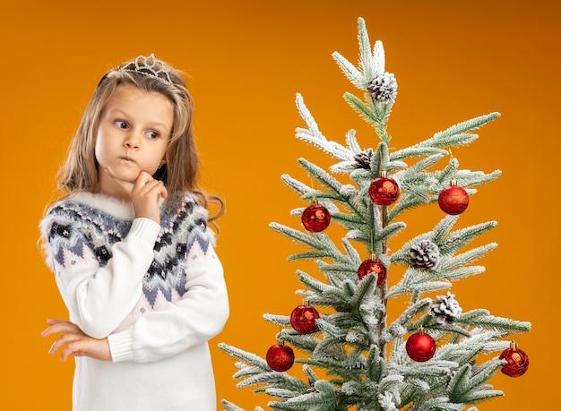 Denkendes kleines mädchen, das in der nähe des weihnachtsbaums steht und eine tiara mit girlande am hals trägt, die die hand unter das kinn legt, isoliert auf der orangefarbenen wand?