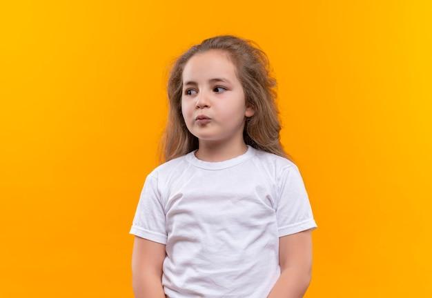 Denkendes kleines schulmädchen, das weißes t-shirt trägt, das seite auf isolierte orange wand betrachtet