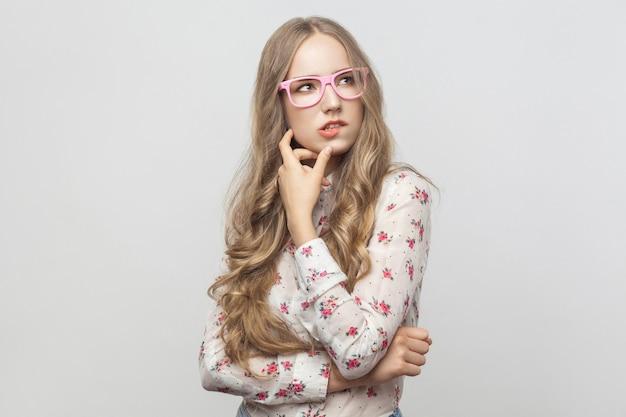 Denkendes konzept. verwirrung langhaarige blonde frau in rosa brille, ihr kinn berühren und aufblicken. studioaufnahme. auf grauem hintergrund isoliert