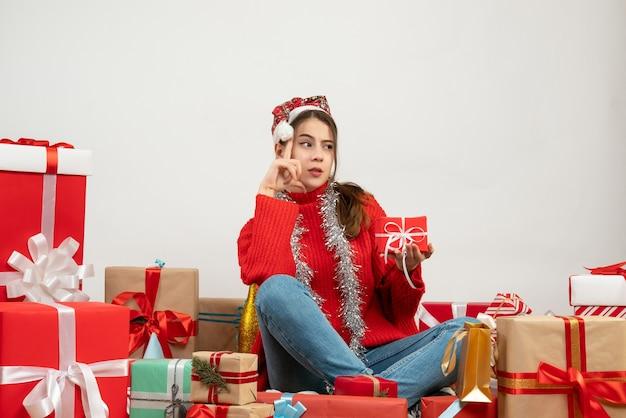 Denkendes partygirl mit weihnachtsmütze, die geschenk hält, das um geschenke auf weiß sitzt