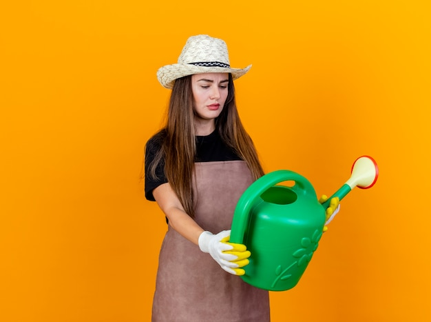 Denkendes schönes gärtnermädchen, das uniform und gartenhut trägt