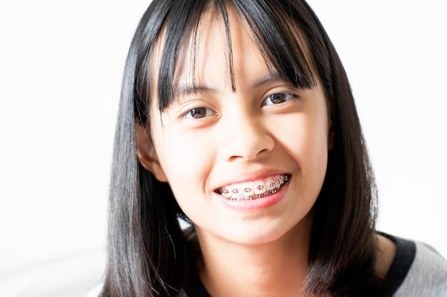 Dental brace girl lächelt und schaut in die kamera, sie fühlt sich glücklich und hat eine gute einstellung zum zahnarzt