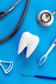 Dentalmodell und zahnärztliche ausrüstung auf blau