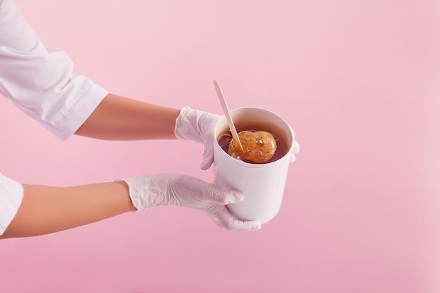 Depilation und haarentfernungskonzept. schließen sie herauf doktor `s hände in den handschuhen und in der medizinischen kleideruniform mit zuckerpaste