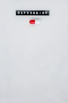 Depressionskennsatz neben roter und weißer kapsel