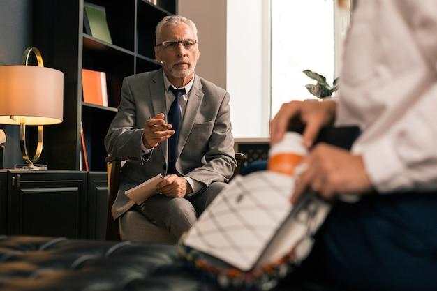 Depressionsmedizin. ernsthafter ruhiger leitender psychotherapeut, der seine hand nach den pillen seiner weiblichen patienten ausstreckt