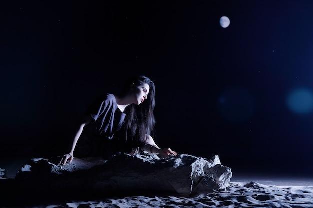 Depressive frau, die in dunkler nacht auf einem stein sitzt. einsamkeit, traurig, emotionskonzept.