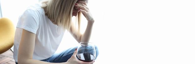Depressive frau sitzt mit gesenktem kopf und hält ein glas wein