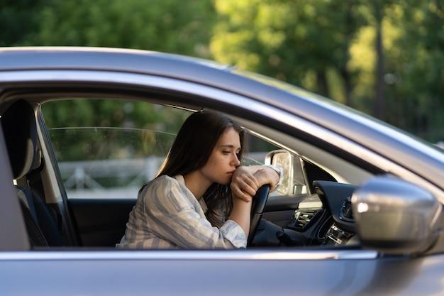 Depressive junge fahrerin sitzt im auto und fühlt sich zweifelhaft verwirrt über schwierige entscheidung, die an persönlichen psychologischen problemen leidet, burnout, streit mit freund, lebenskrise