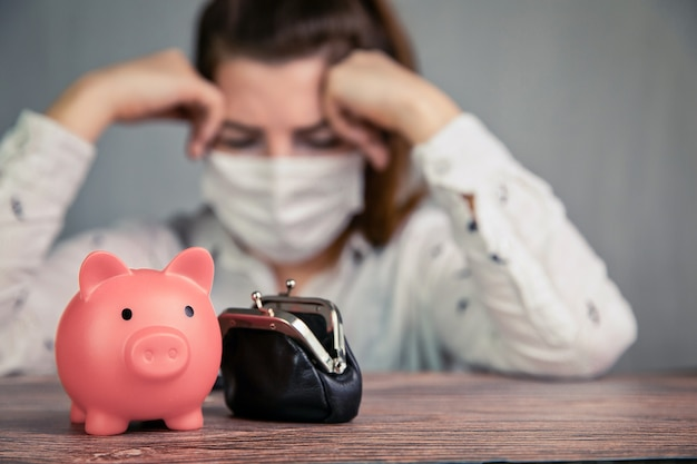 Depressive junge weibliche geschäftsfrau mit rosa sparschwein für ersparnisse und sicherheitsmaske für covid-19