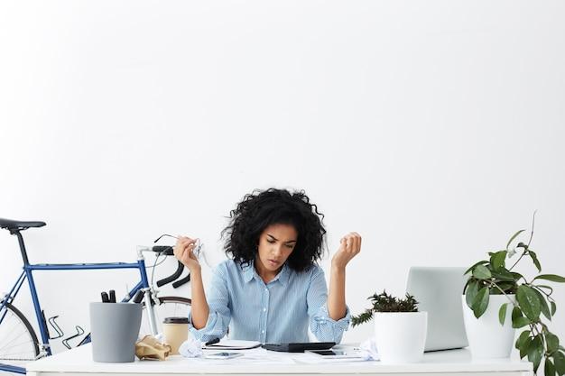 Depressive müde frau, die sich gestresst und erschöpft fühlt, während sie online rechnungen berechnet