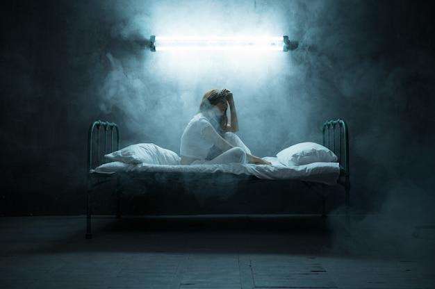 Depressive psychofrau, die im bett sitzt, schlaflosigkeit, dunkles zimmer. psychedelische weibliche person, die jede nacht probleme hat, depression und stress, traurigkeit, psychiatrisches krankenhaus