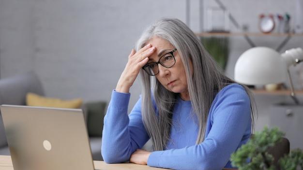 Depressive reife frau erhielt schlechte online-nachrichten. burnout-syndrom, überarbeitung, depression.