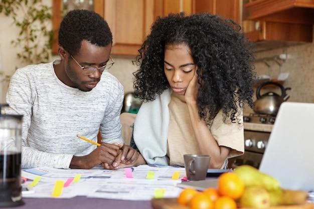 Depressiver arbeitsloser afrikanischer mann in gläsern mit vielen schulden, die die hand seiner unglücklichen frau halten