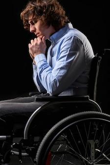 Depressiver behinderter mann hat keinen sinn im leben, er sitzt im rollstuhl, ist mit etwas unzufrieden, schaut nach unten. isoliert auf schwarzem hintergrund. seitenansicht