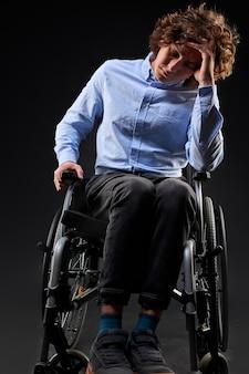 Depressiver behinderter mann hat keinen sinn im leben, er sitzt im rollstuhl, ist mit etwas unzufrieden, schaut nach unten. isoliert auf schwarzem hintergrund